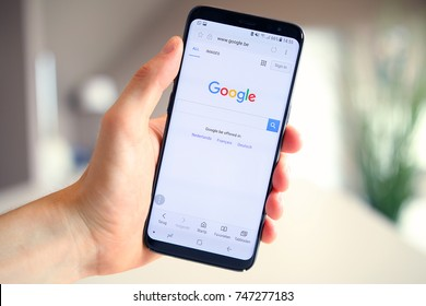 LENDELEDE, BELGIUM - JULY 27TH 2017: a hand holding a brand new Samsung Galaxy S8 mobile phone which displays the Google search engine startpage on the touch screen.An illustrative editorial image.