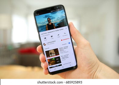 LENDELEDE, BELGIUM - JULY 28TH 2017: a hand holding a new Samsung Galaxy S8 mobile phone which displays the Despacito song on the Youtube app. An illustrative editorial image on an interior background