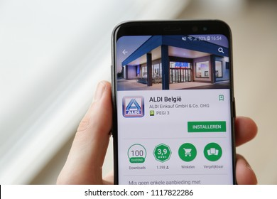 LENDELEDE, BELGIUM - MARCH 24TH 2018: a hand holding a Samsung Galaxy S8 mobile phone which displays the Aldi shopping app on the touch screen. Illustrative editorial image on an interior background