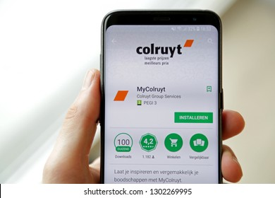 LENDELEDE, BELGIUM - MARCH 24TH 2018:a hand holding a Samsung Galaxy S9 mobile phone which displays the Colruyt shopping app on the touch screen. Illustrative editorial image on an interior background