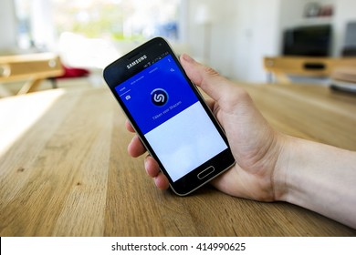 LENDELEDE, BELGIUM - MAY 02TH 2016: a hand holding a Samsung Galaxy S5 mini mobile phone which displays the Shazam app. Illustrative editorial image on a decorated interior background.