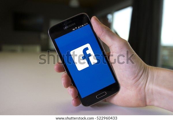 LENDELEDE, BELGIUM - MAY 24TH 2016: a hand holding a Samsung Galaxy S5 mini mobile phone which displays the Facebook app on the touch screen.An illustrative editorial image on an interior background.