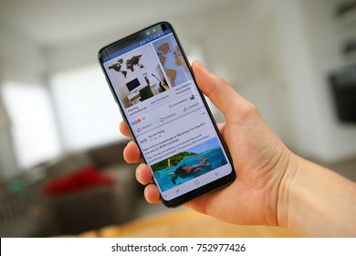 LENDELEDE, BELGIUM - NOVEMBER 24TH 2017: a hand holding a Samsung Galaxy S8 mobile phone which displays the Facebook app on the touch screen. An illustrative editorial image on an interior background.