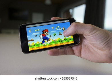 LENDELEDE, BELGIUM - NOVEMBER 28TH 2016: A hand holding a smartphone with the Super Mario Run game on the reflective touch screen. An illustrative editorial image on an interior design background.