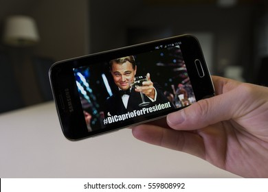 LENDELEDE, BELGIUM - NOVEMBER 28TH 2016: a hand holding a Samsung Galaxy S5 mini mobile phone with the popular DiCaprio For President meme. An illustrative editorial image on an interior background.