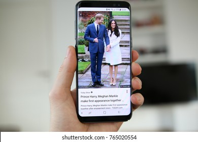 LENDELEDE, BELGIUM- NOVEMBER 29TH 2017: a hand holding a new Samsung Galaxy S8 mobile phone which displays the engagement of Prince Harry and Meghan Markle on the touch screen. Illustrative editorial.