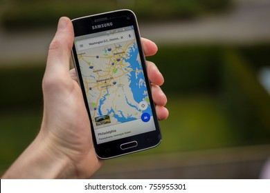 LENDELEDE, BELGIUM - OCTOBER 28TH 2017: a hand holding a brand new Samsung Galaxy S8 mobile phone with the Google Maps app, with Washington. Illustrative editorial image on an interior background.