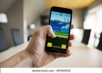 LENDELEDE, BELGIUM - SEPTEMBER 13TH 2016: A hand holding a smartphone with the Super Mario Run game on the reflective touch screen. An illustrative editorial image on an interior design background.