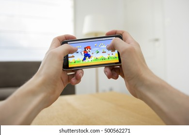 LENDELEDE, BELGIUM - SEPTEMBER 13TH 2016: Two hands holding a smartphone with the Super Mario Run game on the touch screen. An illustrative editorial image on an interior design background.