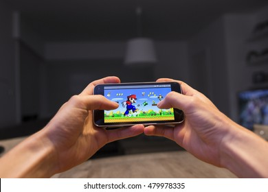 LENDELEDE, BELGIUM - SEPTEMBER 7TH 2016: Two hands holding a smartphone with a Super Mario game on the touch screen. The room in the background is dark. An illustrative editorial image.