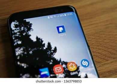 LENDELEDE, BELGIUM-APRIL 6TH 2019:Hand holding a Samsung Galaxy S9 mobile phone which displays the PayPal app logo on the homescreen of the touch screen.Other icons are visible.Illustrative editorial