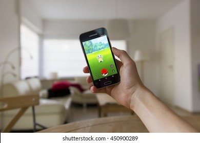 LENDELEDE, BELGIUM-JULY 11TH 2016:a hand holding a Samsung Galaxy S5 mini mobile phone which displays the Pokemon Go app on the touch screen.An unaltered illustrative editorial image in a living room.