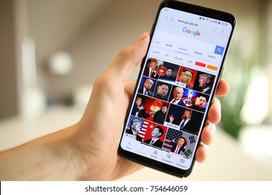 LENDELEDE,BELGIUM-AUGUST 26TH 2017:hand holding a Samsung Galaxy S8 mobile phone which displays pictures of Trump and Kim Jong-Un. Nuclear conflict. Illustrative editorial image on interior background