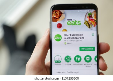 LENDELEDE,BELGIUM-FEBRUARY 24TH 2018: hand holding a new Samsung S9 phone which displays the Uber Eats food delivery app on the touch screen. Illustrative editorial image on an interior background