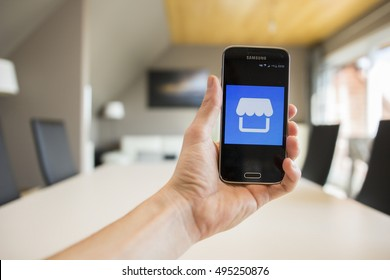 LENDELEDE,BELGIUM-OCTOBER 8TH 2016:A hand holding a Samsung Galaxy S5 mini smartphone with the logo of Facebook Marketplace on the touchscreen.An illustrative editorial image on an interior background