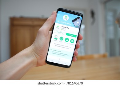 LENDELEDE,BELGIUM-SEPTEMBER 14TH 2017:hand holding a brand new Samsung Galaxy S8 mobile phone which displays the Android Pay app on the touch screen.Illustrative editorial image on interior background