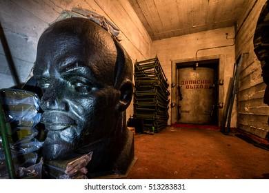Lenin monument in abandoned ex Soviet underground cold war bomb shelter. Lenins head. Symbols of Soviet Union. Symbol of communism. Urban exploration. Extreme tourism. USSR. Text: emergency exit.