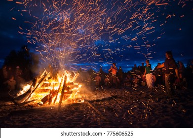 Leningrad Oblast, Russia - July 14, 2015: Big  tourist bonfire on the beach  during the festival. Young people dance and sing around the campfire. Deep night.