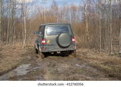 LENINGRAD REGION , RUSSIA - APRIL 16, 2016: Off-road car UAZ-Patriot sneaking through the muddy forest road
