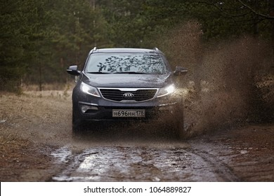 Leningrad Region, Russia - April 2017: A black car Kia Sportage  is driving through a puddle with splashes. A dirt road in a pine forest. Suv Kia Sportage front view