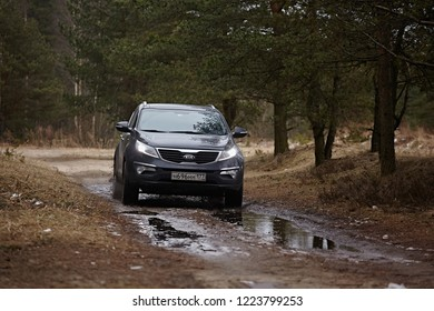Leningrad Region, Russia - April 2017: A black car is driving through a puddle with splashes. A dirt road in a pine forest. Suv Kia Sportage front view