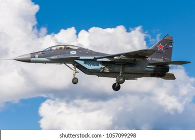 LENINGRAD REGION, RUSSIA - AUGUST, 2017: military bomber MIG 29 of Russian air force perfoming landing to the airbase runway in Russia. Air fighter flying around base. War plane on the blue cloudy sky