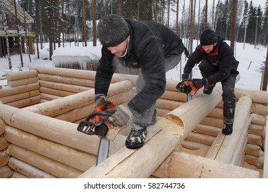 Leningrad Region, Russia - February 2, 2010: Construction log house in winter outdoors, workers make notches on logs using chainsaws.