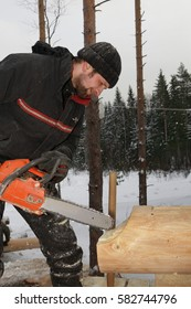 Leningrad Region, Russia - February 2, 2010:  Woodworker is brushed saddle notch with chainsaw on log cabin wall.