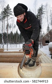 Leningrad Region, Russia - February 2, 2010: Builder handles log using chainsaw, He cut out round saddle notch.