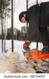 Leningrad Region, Russia - February 2, 2010: Corner notch, cutting and brushing for log cabin construction, using chainsaw.