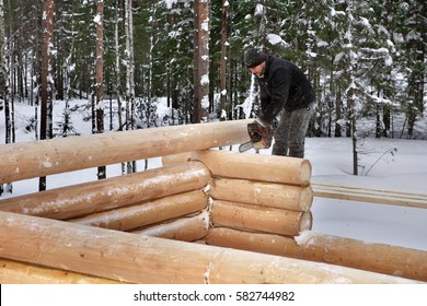 Leningrad Region, Russia - February 2, 2010: building process, log home corner notching, Worker processes timber using a chainsaw.