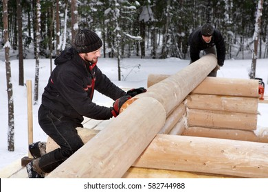 Leningrad Region, Russia - February 2, 2010: Log Home Construction Handcrafting, two workers doing assembly of the wall made of logs.