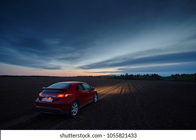 Leningrad Region, Russia - May  2017: A red Honda Civic car rides along a dirty road and fields in the countryside. The lights from the headlights are on. Landscape with the sky in the the night.