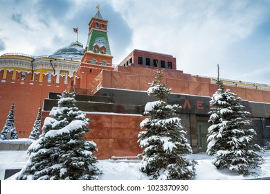 Lenin's Mausoleum by Moscow Kremlin on the Red Square in winter during snowfall in Moscow, Russia. The inscription is Lenin. The Red Square is the main tourist attraction of Moscow.