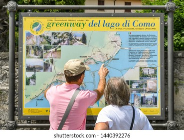 LENNO, LAKE COMO, ITALY - JUNE 2019: People looking at a map of the Greenway del lago di Como in Lenno on Lake Como. The Greenway is a walking trail which runs for several miles around the lake.
