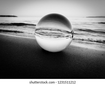 Lens ball on the beach reflecting waves in black and white.