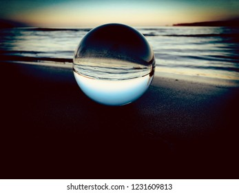 Lens ball on beach reflecting waves and a blue bright sky inside the glass, colorful with dark vignette.