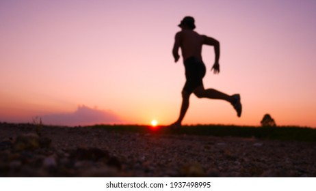 Lens blurred silhouette for a runner training in the evening. Sunsets