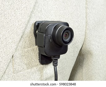 lens from the camcorder, security police body camera with power cord in black color on a white suit jacket