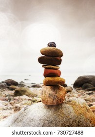 Lens defect. Balanced stone pyramid on sea shore, waves in background. Colorful flat stones for meditation lying on sea