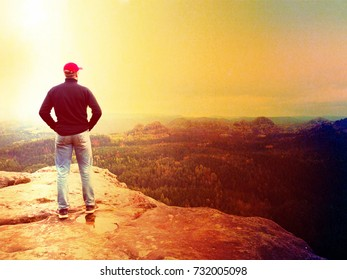 Lens defect. Hiker man stays on a rocky ridge and enjoy view over long valley to horizon. Cold Sun hidden in clouds. National park with a  rocky mountains and  valleys.