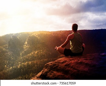 Lens defect. Man meditating in Lotus Pose on rocky cliff. Sportsman practicing Yoga on stone edge above landscape