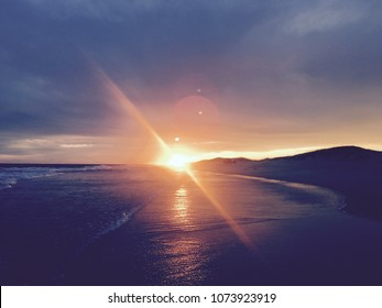Lens flair and sun setting below dunes on a beach. Yellow sky reflected in ocean water. Silhouetted landscape