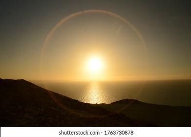 a lens flare around the setting sun  along the welsh coast line over the horizon reflecting in the sea