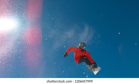 LENS FLARE, BOTTOM UP: Bright winter sun shines on snowboarder doing a spinning grab trick. Awesome bottom up view of the pro athlete doing a difficult grab trick on his snowboard on sunny winter day.