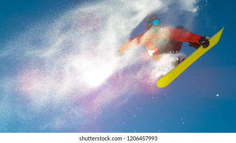 LENS FLARE, BOTTOM UP: Pro snowboarder dude leaves a trail of snow in air while doing a trick. Athletic male tourist having fun snowboarding and doing tricks during his active winter holiday in Alps.