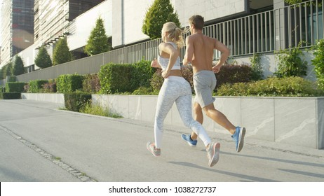 LENS FLARE: Caucasian man and woman with athletic physiques running in the sunny city. Unrecognizable fit couple enjoying their early morning jog. Athletic people exercising outdoors in the city.