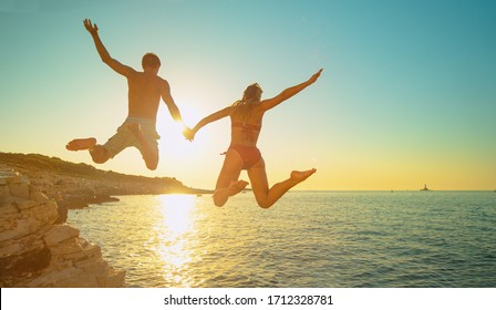 LENS FLARE: Cheerful Caucasian woman holds her boyfriend's hand as they jump off a cliff and into the sea at golden sunset. Fit and carefree tourists hold hands while jumping into sea at sunset.