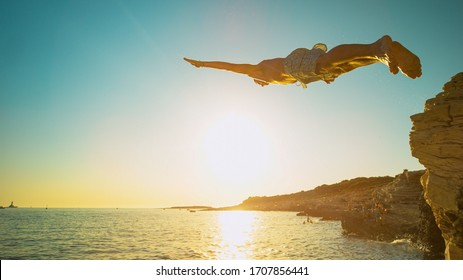 LENS FLARE, CLOSE UP: Athletic man dives off a cliff and head-first into the ocean at sunset. Fit male tourist on vacation jumps of a rocky ledge and dives into the refreshing sea water in Croatia.