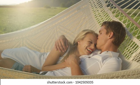 LENS FLARE, CLOSE UP: Joyful man tenderly kisses blonde woman on her forehead while lying in romantic sling. Lovely boyfriend and girlfriend snuggling in hammock on a sunny spring day in countryside.